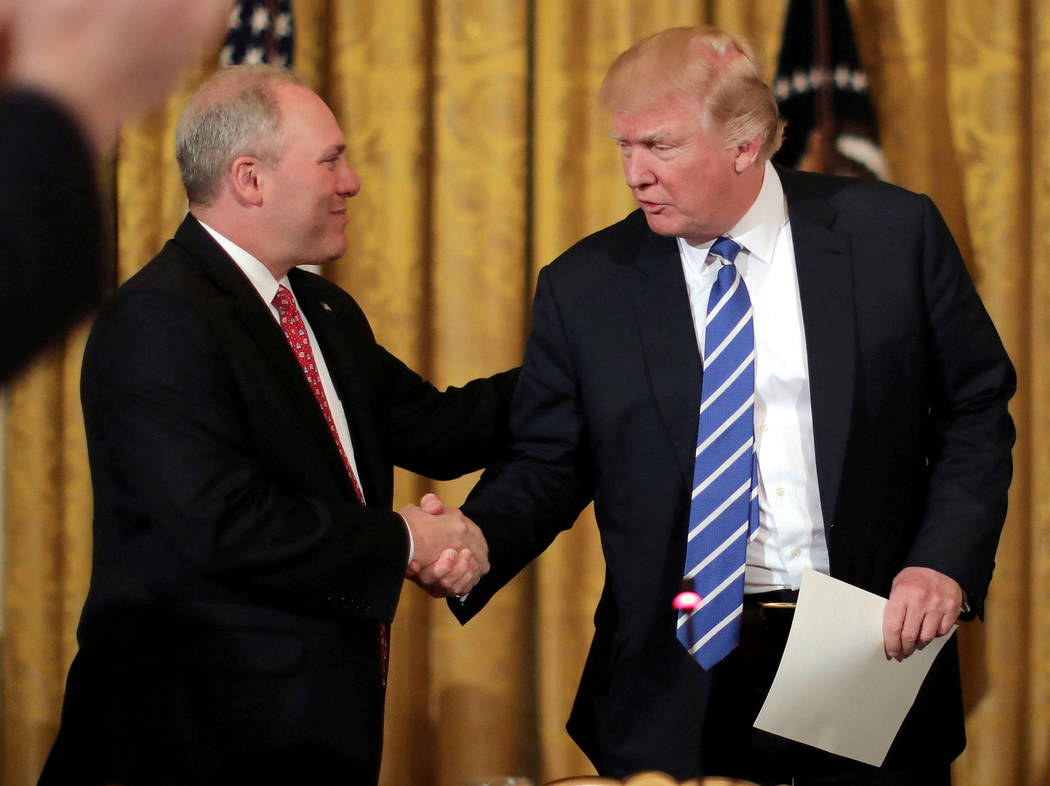 FILE PHOTO - U.S. President Donald Trump shakes hands with House Majority Whip Steve Scalise (L) as he attends a meeting with the U.S. House Deputy Whip team in the East room of the White House in ...