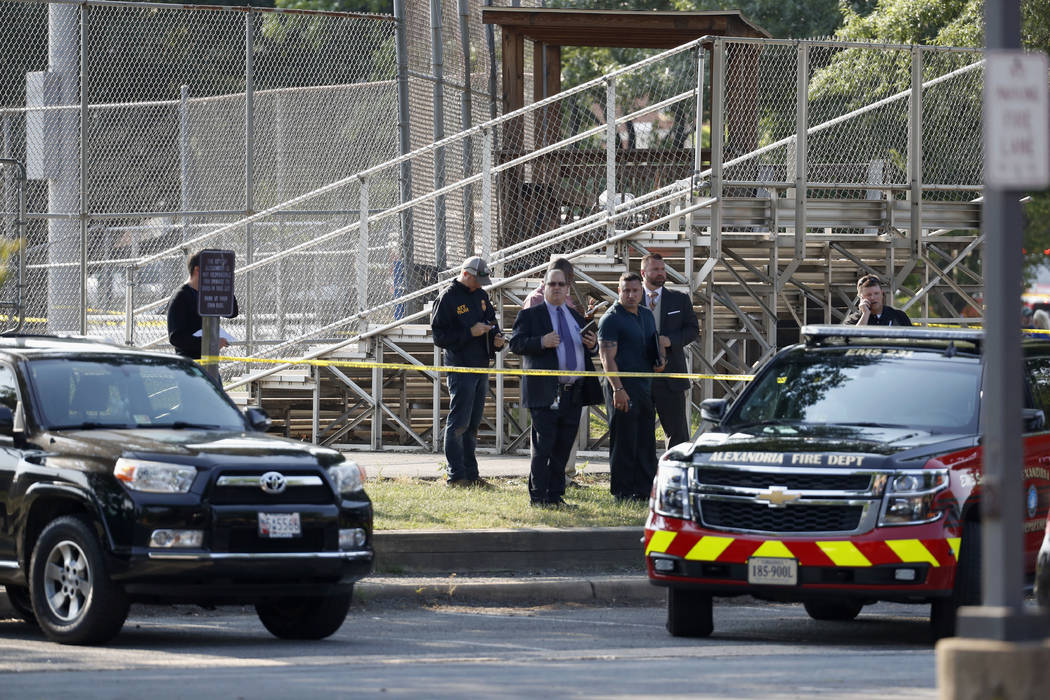 Law enforcement officers investigate the scene of a shooting near a baseball field in Alexandria, Va., Wednesday, June 14, 2017, where House Majority Whip Steve Scalise of La. was shot at a Congre ...