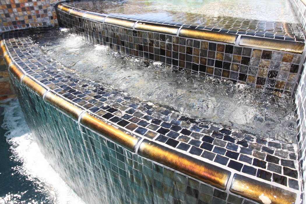 Mary Vail A splash of color was accomplished with 6-inch, quarter-round gold iridescent accent tile on the tiered spa spillway.