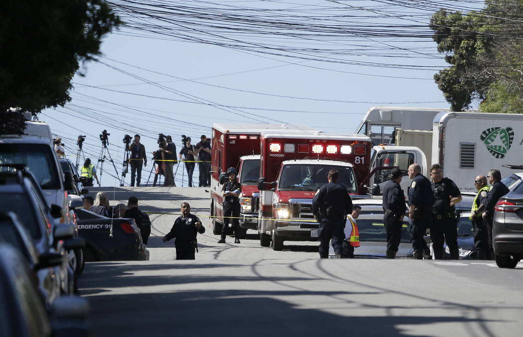 Emergency vehicles are parked and police gather outside a UPS package delivery warehouse where a shooting took place Wednesday, June 14, 2017, in San Francisco. A UPS spokesman says four people we ...