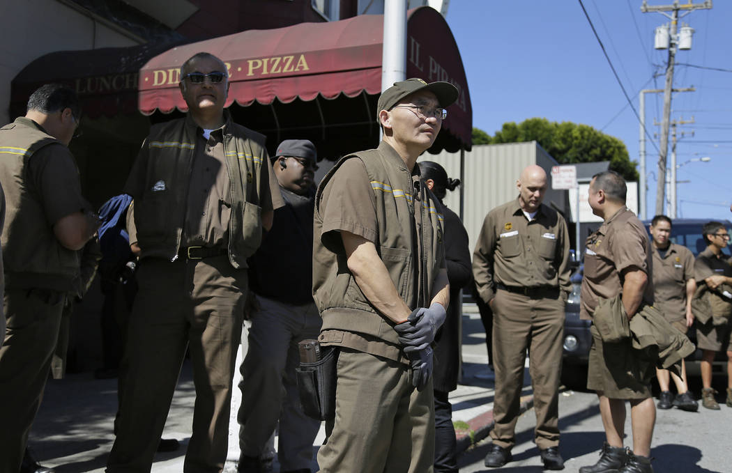 UPS workers gather outside a UPS package delivery warehouse where a shooting took place Wednesday, June 14, 2017, in San Francisco. A UPS spokesman says four people were injured in the shooting at ...