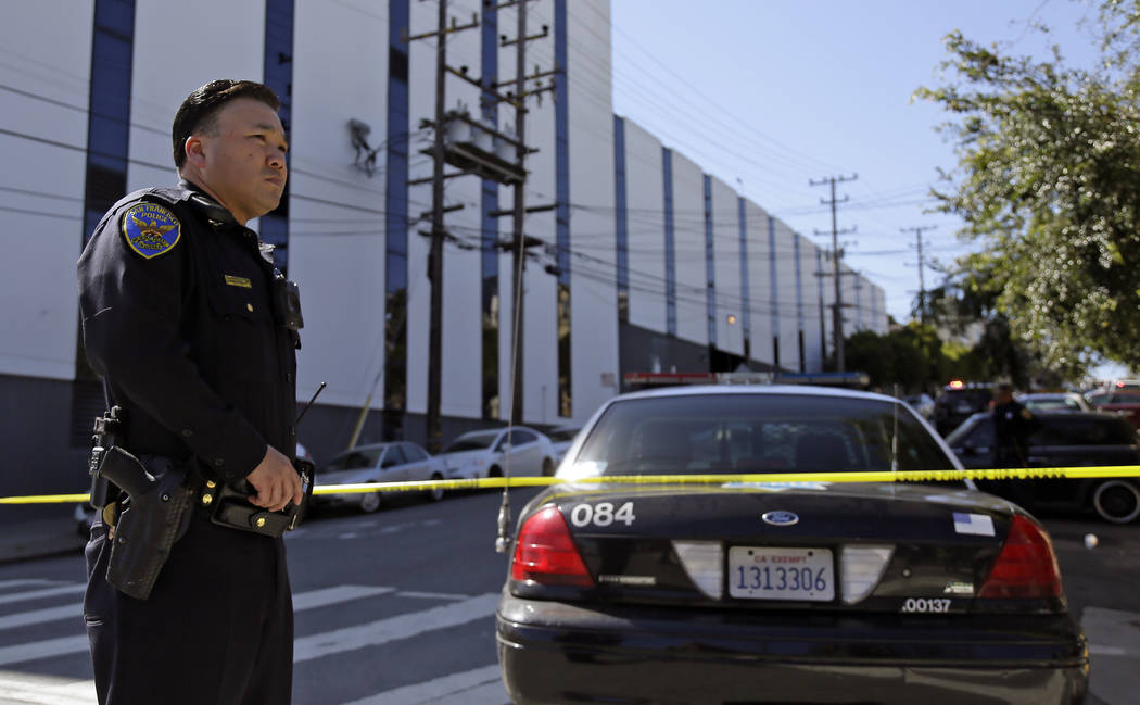 A San Francisco police officer stands watch outside a UPS package delivery warehouse where a shooting took place Wednesday, June 14, 2017, in San Francisco. A UPS spokesman says four people were i ...