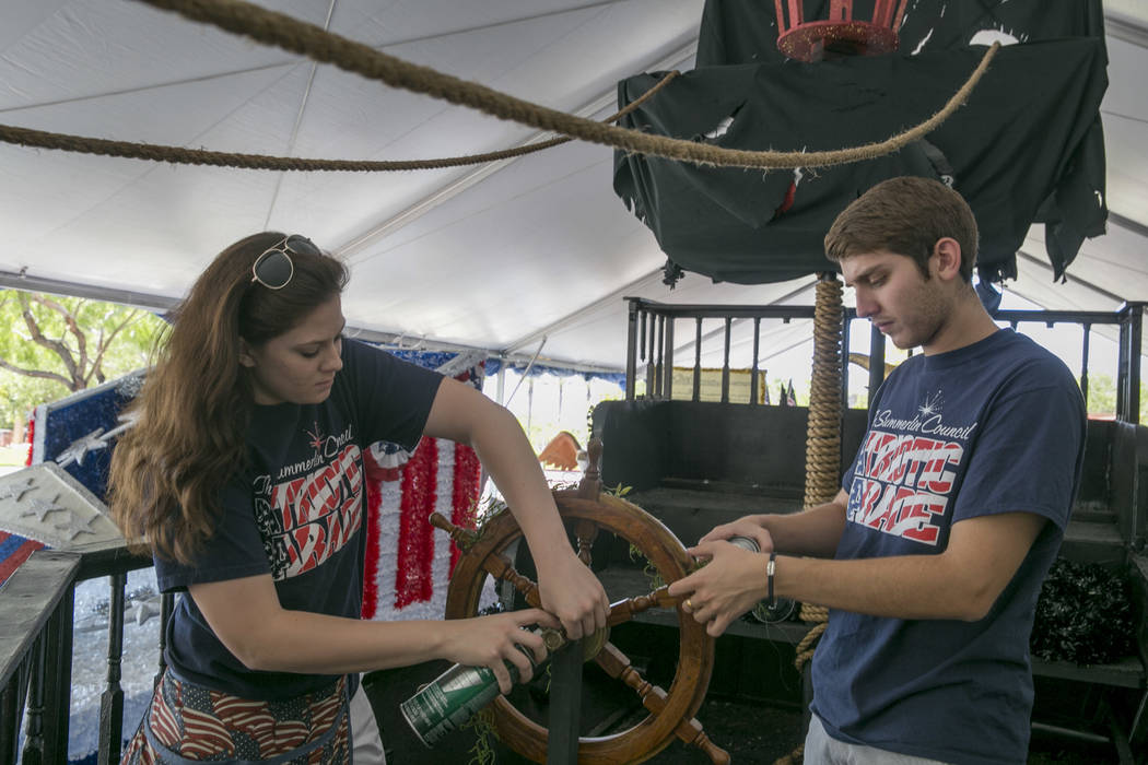 From left: Stephanie Day and Sam Bell, volunteers for the Summerlin Council Patriotic Parade, put the finishing touches on a pirate-themed float at Trails Park in Summerlin, Friday, June 30, 2017. ...