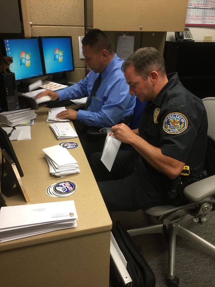 Public Information Officers Rod Pena (Left) and Scott Williams (Right) prepare C.A.P.T.U.R.E. stickers to mail to the Henderson residents who have registered for the surveillance program. (Michell ...