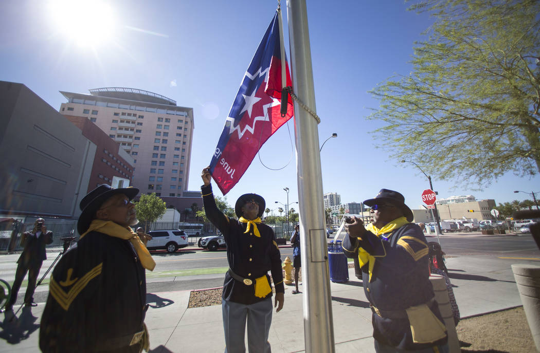 Members of the Southern Nevada Buffalo Soldiers 9th and 10th Horse Cavalry Association Keith Hill, left, Kelly Hawthorne and Jon Jon Everet raise the official Juneteenth flag during a ceremony out ...