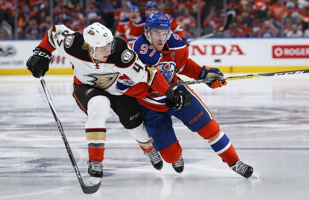 Anaheim Ducks' Hampus Lindholm, left, from Sweden, and Edmonton Oilers' Connor McDavid race for the puck during the second period of Game 4 of an NHL hockey second-round playoff series, Wednesday, ...