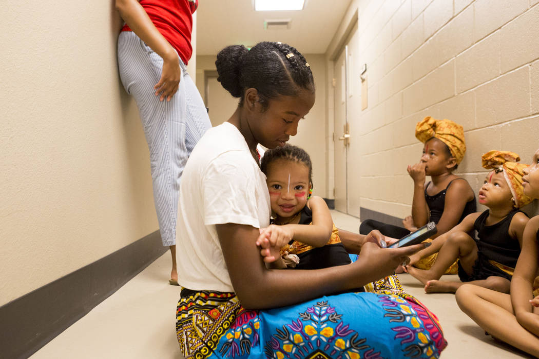 Co-instructor for Olabisi African Dance Ensemble Tuwani Palacio, 16, holds performer Makayla Williams, 2, before the ensemble preforms during the National Juneteenth Observance celebration of June ...