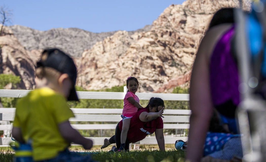 Fairon Quick demonstrates a pose with her daughter Caitlin, 3, on her back during a family yoga class at Spring Mountain Ranch State Park on Wednesday, June 14, 2017.  Patrick Connolly Las Vegas R ...