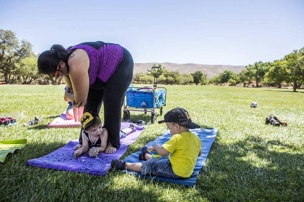 Dominic Wolf, 3, plays between his mother Anjelica's legs while his brother Vincent, 2, watches during a family yoga class at Spring Mountain Ranch State Park on Wednesday, June 14, 2017.  Patrick ...