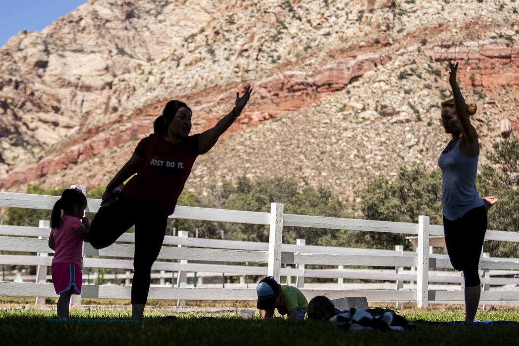 Fairon Quick, left, demonstrates a pose with her daughter Caitlin, 3, nearby during a family yoga class at Spring Mountain Ranch State Park on Wednesday, June 14, 2017.  Patrick Connolly Las Vegas ...