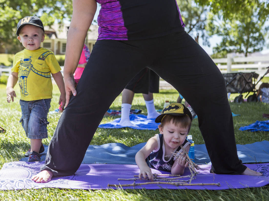 Dominic Wolf, 3, plays on a yoga mat while his mother Anjelica works on a pose and his brother Vincent, 2, watches during a family yoga class at Spring Mountain Ranch State Park on Wednesday, June ...