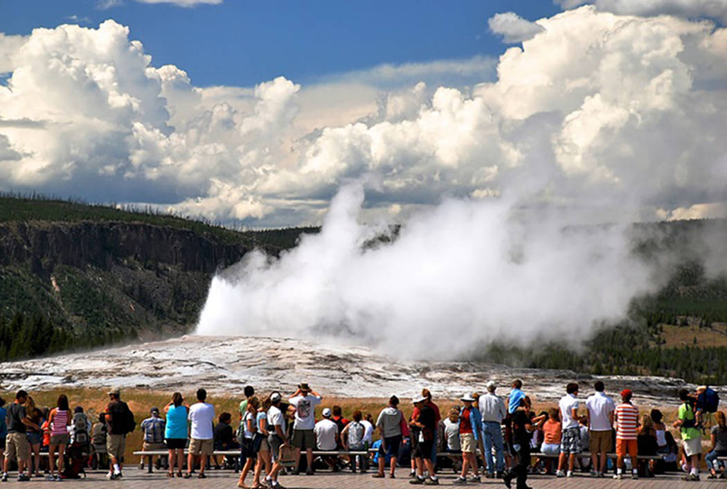 Visitors watch a geyser at Yellowstone National Park (Courtesy)