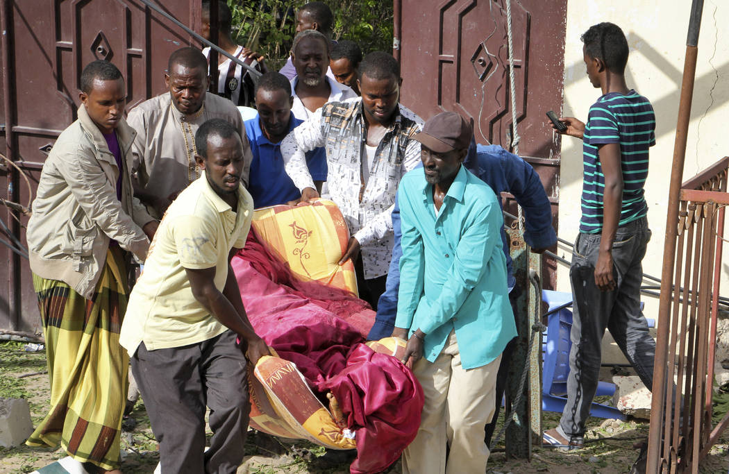 Somali men carry away the body of a civilian who was killed in a militant attack on a restaurant in Mogadishu, Somalia Thursday, June 15, 2017. Somali survivors early Thursday described harrowing  ...