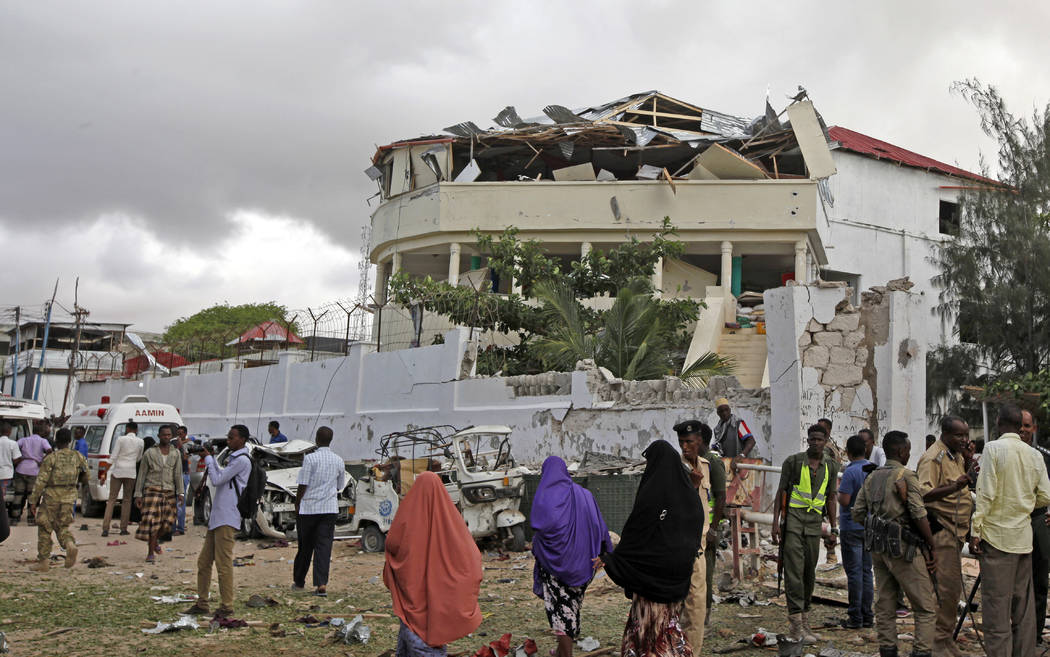 Somalis gather outside a destroyed building near a restaurant that was the scene of a car bomb blast and gun battle in Mogadishu, Somalia Thursday, June 15, 2017. Somali survivors early Thursday d ...