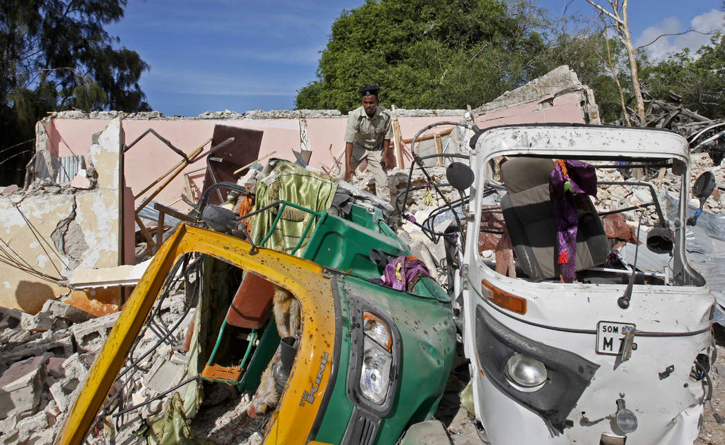 A member of Somalia's security forces walks past destroyed vehicles at the scene of a car bomb blast and gun battle targeting a restaurant in Mogadishu, Somalia Thursday, June 15, 2017. Somali sur ...