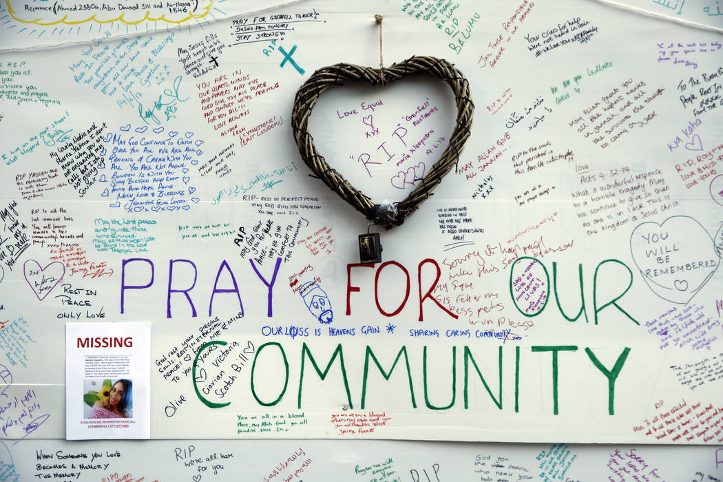 Messages of support for those affected by the massive fire in Grenfell Tower are displayed on a well near the tower in London, Thursday, June 15, 2017. A massive fire raced through the 24-story hi ...