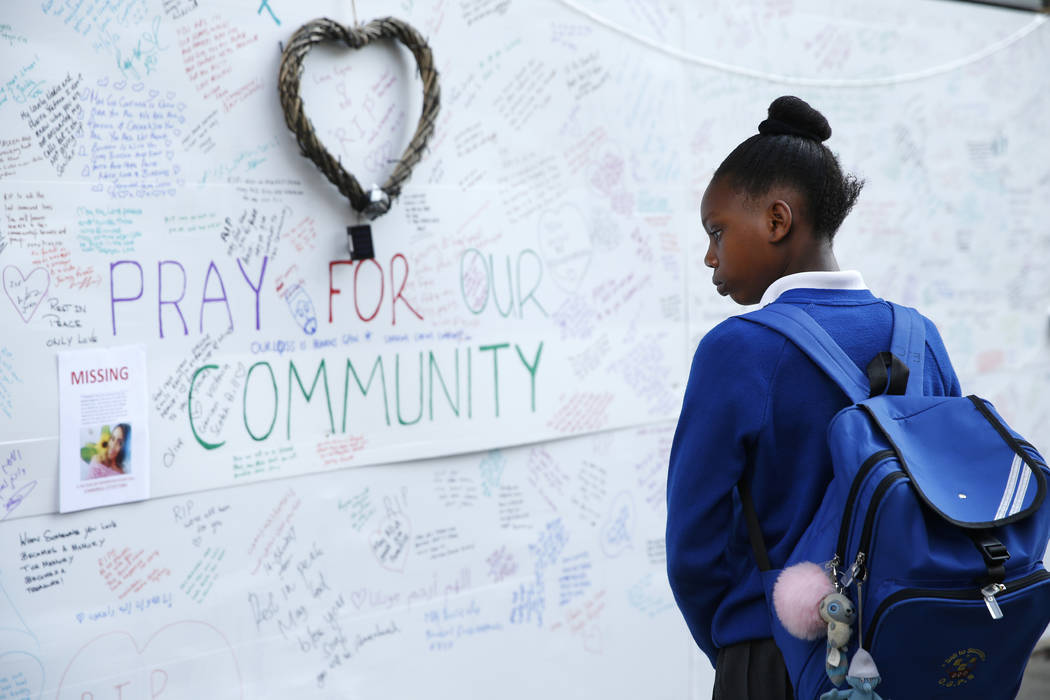 A schoolgirl looks at messages of support for those affected by the massive fire in Grenfell Tower, in London, Thursday, June 15, 2017. A massive fire raced through the 24-story high-rise apartmen ...