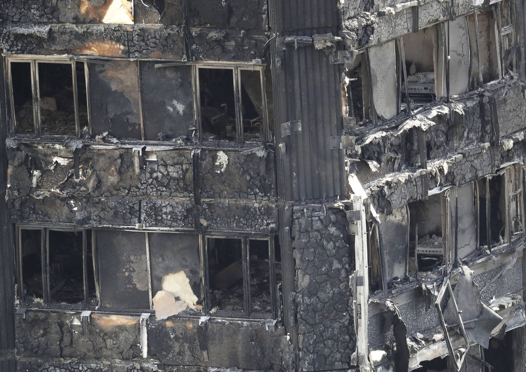 Part of the scorched facade of the Grenfell Tower in London as firefighting continue to damp-down the deadly fire, Thursday, June 15, 2017.  A massive fire raced through the 24-storey high-rise ap ...