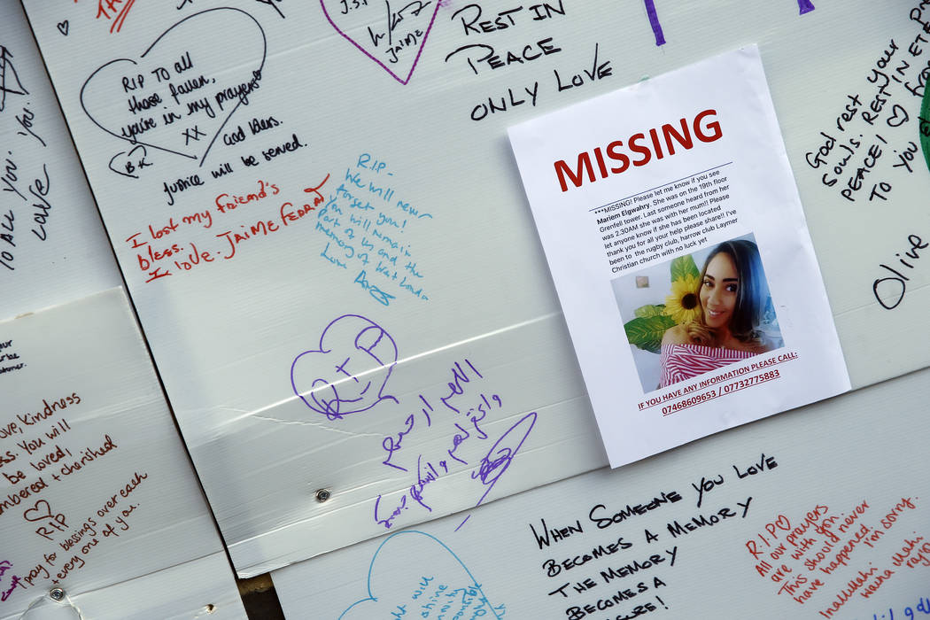 A schoolgirl looks at messages of support for victims, missing and those affected by the massive fire in Grenfell Tower, in London, Thursday, June 15, 2017. A massive fire raced through the 24-sto ...