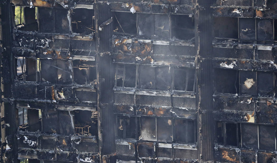Remains of furniture are seen through windows of the burnt down Grenfell Tower in London, Thursday, June 15, 2017. A massive fire raced through the 24-story high-rise apartment building in west Lo ...