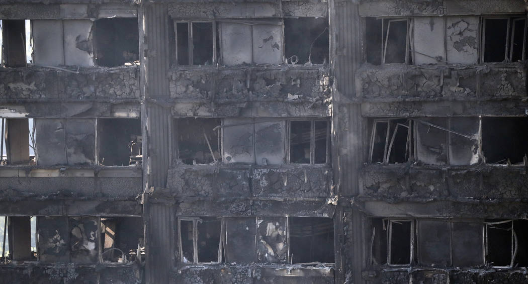 Remains of furniture are seen through the windows as smoke still emerges from the charred Grenfell Tower in London, Thursday, June 15, 2017. A massive fire raced through the 24-story high-rise apa ...