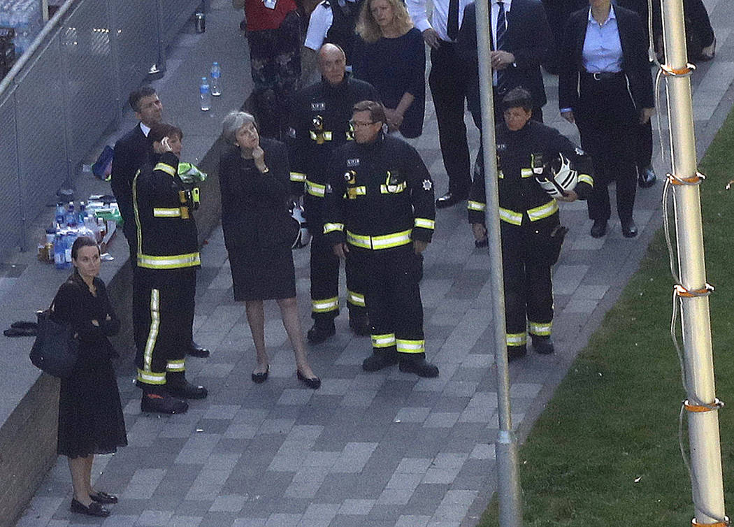 Britain's Prime Minister Theresa May, center, speaks to firefighters after arriving at Grenfield Tower in London, Thursday, June 15, 2017, following a deadly fire in the apartment block.  A massiv ...