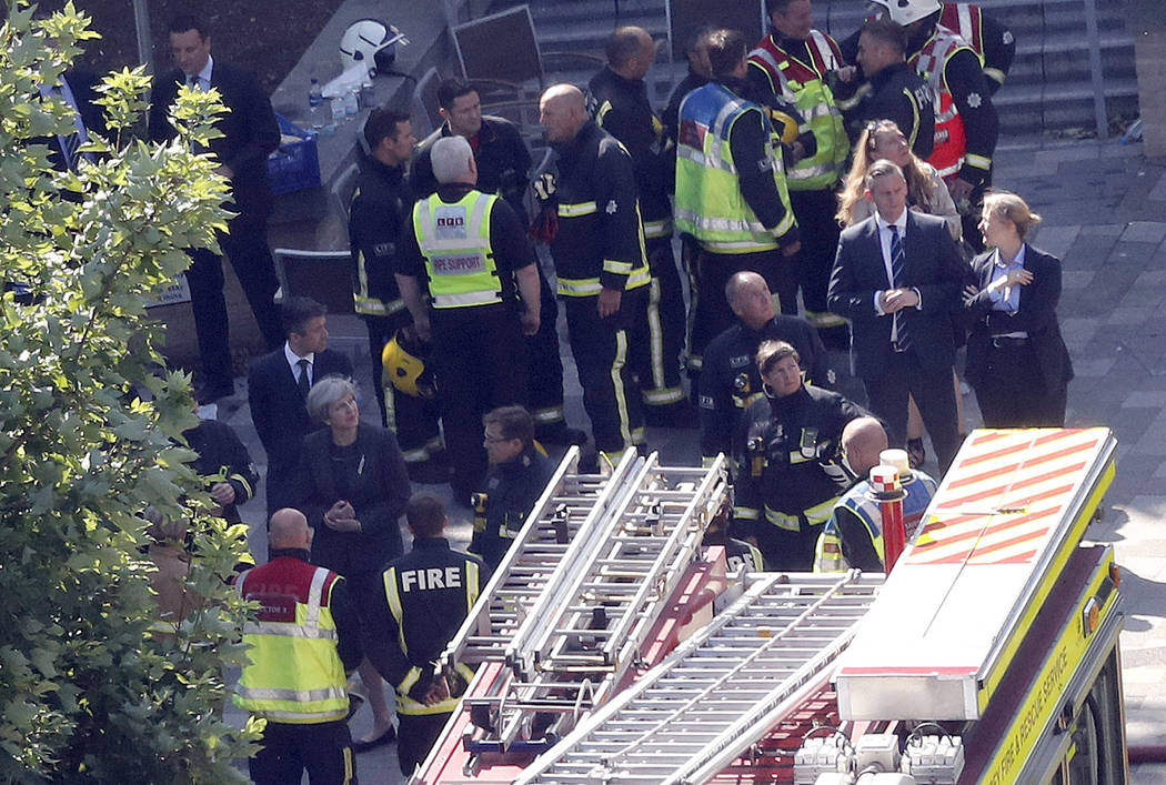 Britain's Prime Minister Theresa May, bottom left, speaks to firefighters and police officers after arriving at Grenfield Tower in London, Thursday, June 15, 2017, following a deadly fire in the a ...