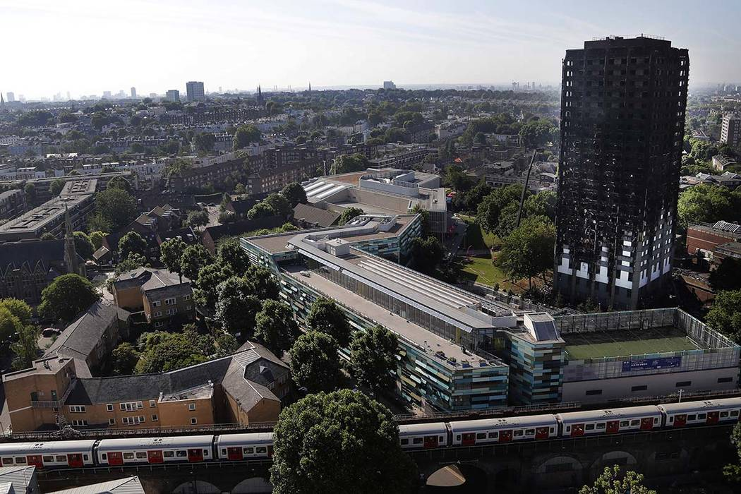 The remains of the charred Grenfell Tower stands in London, Thursday, June 15, 2017 as a train passes by. A massive fire raced through the 24-story high-rise apartment building in west London earl ...