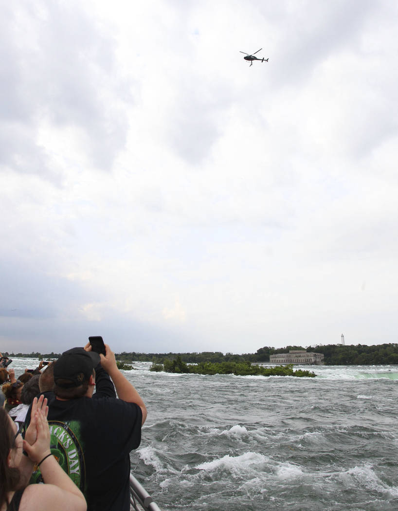 Spectators watch as Erendira Wallenda performs a series of acrobatic maneuvers, including hanging by her teeth, while suspended from a helicopter above Niagara Falls in Niagara Falls, N.Y., Thursd ...