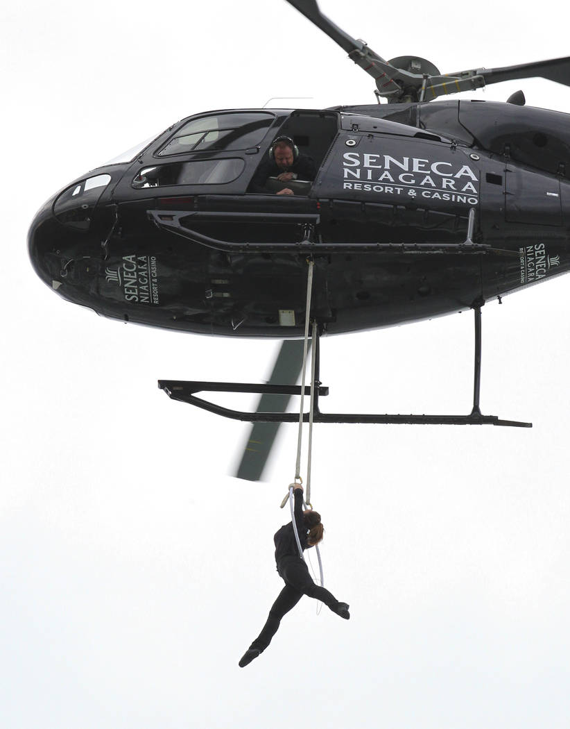 Nik Wallenda watches from above as his wife, Erendira Wallenda, hangs by her teeth while suspended from a helicopter above Niagara Falls in Niagara Falls, N.Y., Thursday, June 15, 2017.   Erendira ...