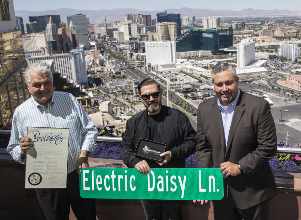 "Clark County Commissioner Steve Sisolak, left, and Chris Baldizan, MGM Senior Vice President of Entertainment, right, present Insomniac founder/CEO Pasquale Rotella with a ""Key to the Strip"" d ..."