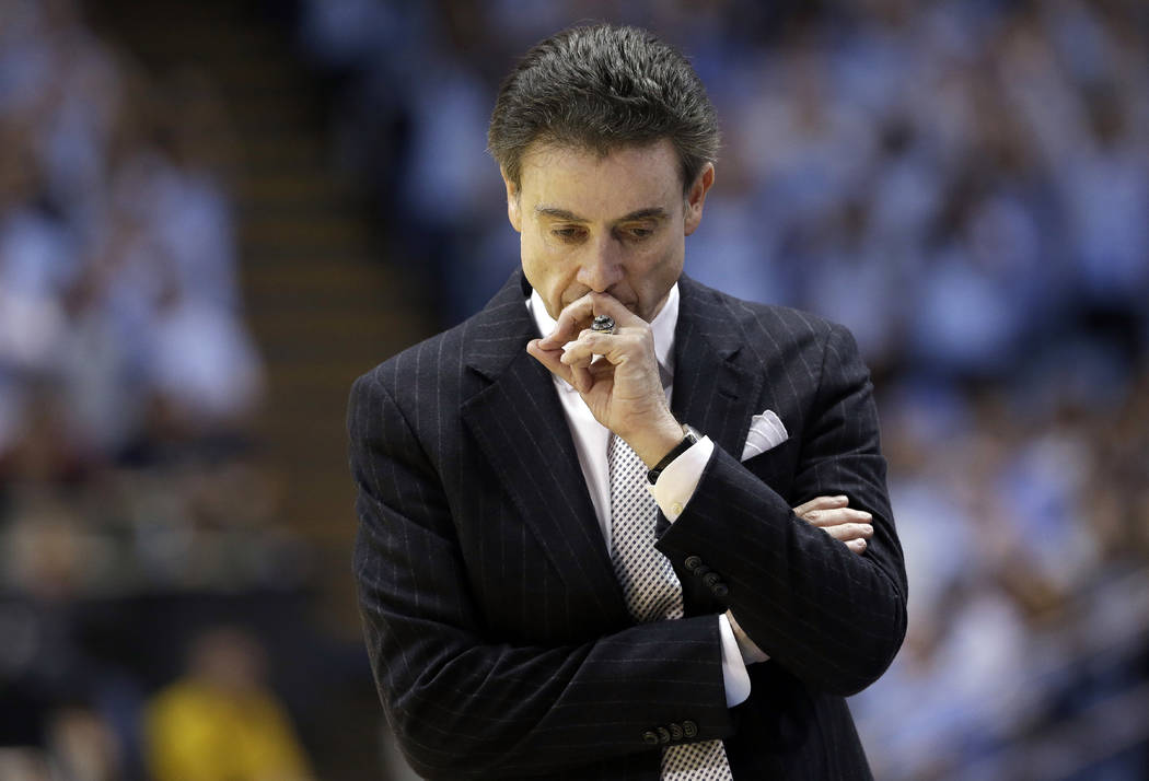 FILE- In this Jan. 10, 2015, file photo, Louisville's coach Rick Pitino pauses during the first half of an NCAA college basketball game against North Carolina in Chapel Hill, N.C. The NCAA suspend ...
