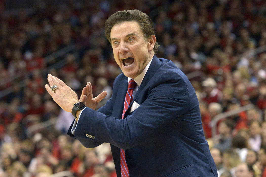 Louisville head coach Rick Pitino sends a play in to his team during the first half of an NCAA college basketball game against Syracuse, Wednesday, Feb. 17, 2016, in Louisville Ky. Louisville won  ...