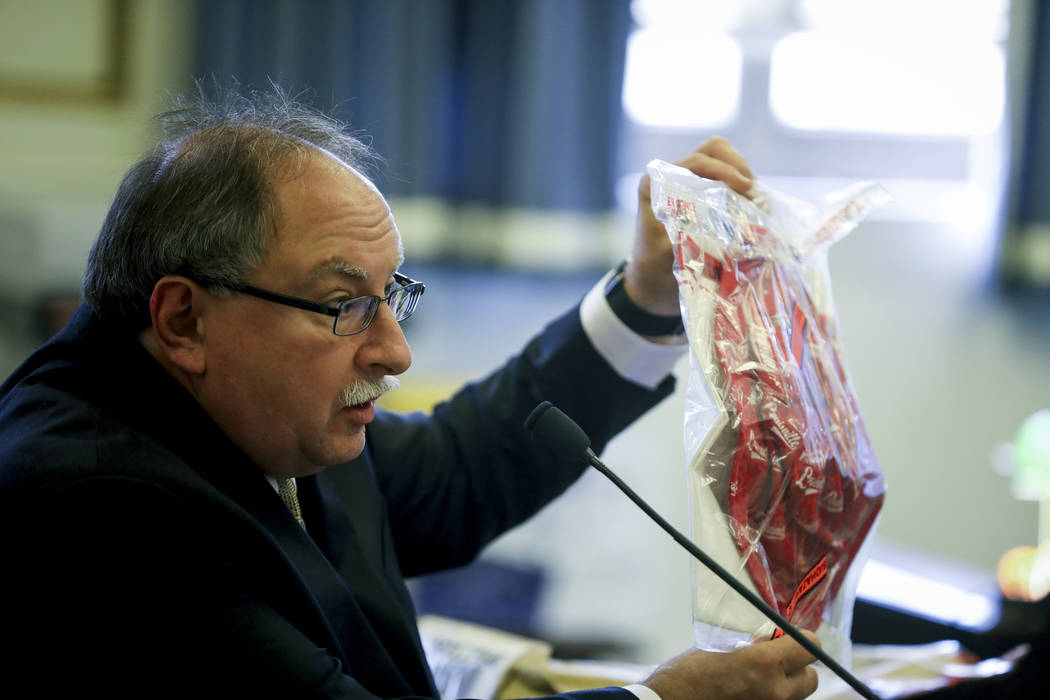 Edward Lattyak, firearms expert with the Hamilton County coroner's office, shows Sam DuBose's red hat with a bullet hole, during the retrial of former University of Cincinnati police officer Raymo ...
