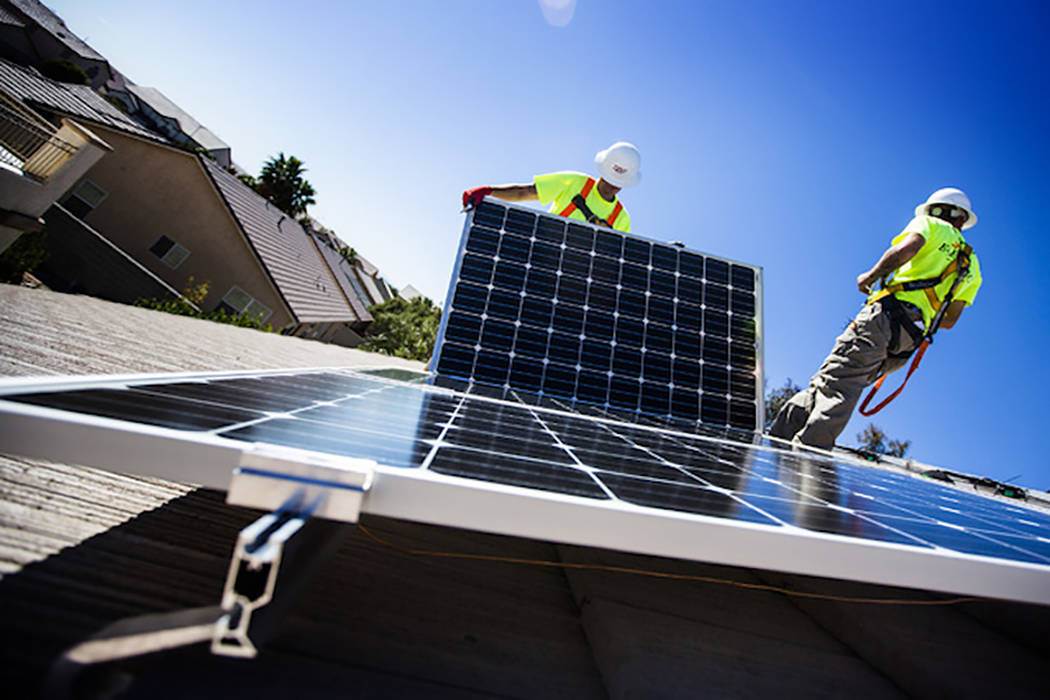 Matt Neifeld,left, and Jacy Sparkman with Robco Electric installs solar panels at a home in northwest Las Vegas. (Jeff Scheid Las Vegas Review-Journal)