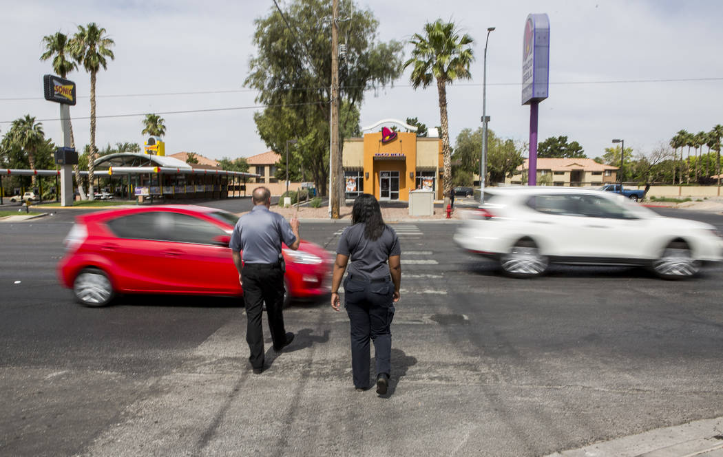 Cars whiz by on Nellis Boulevard as Officer Robert Mayer of the Clark County School District Police and Shae Moore, an EMT with Community Ambulance, begin to cross at the intersection of Nellis an ...