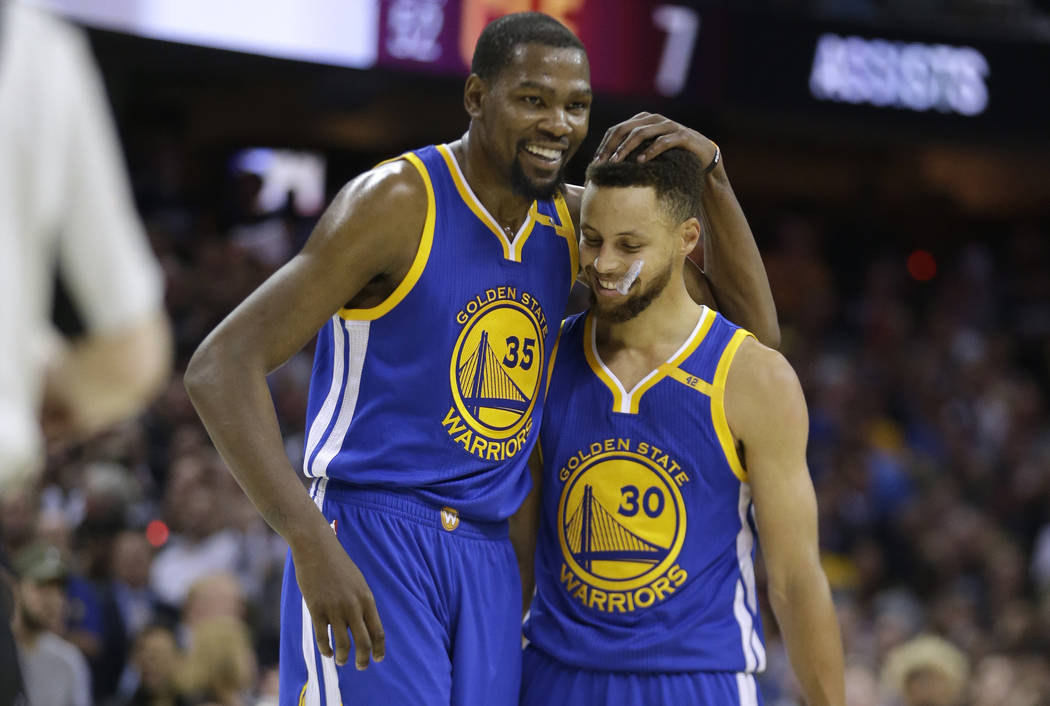 Golden State Warriors' Kevin Durant (35) hugs teammate Stephen Curry (30) during the first half of Game 4 of basketball's NBA Finals against the Cleveland Cavaliers in Cleveland, Friday, June 9, 2 ...