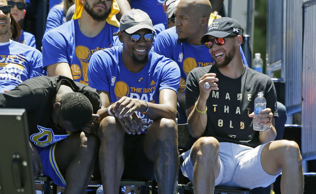 From left, Draymond Green, Kevin Durant and Stephen Curry laugh during their rally for winning the NBA championship Thursday, June 15, 2017, in Oakland, Calif. Oakland is celebrating its second ch ...