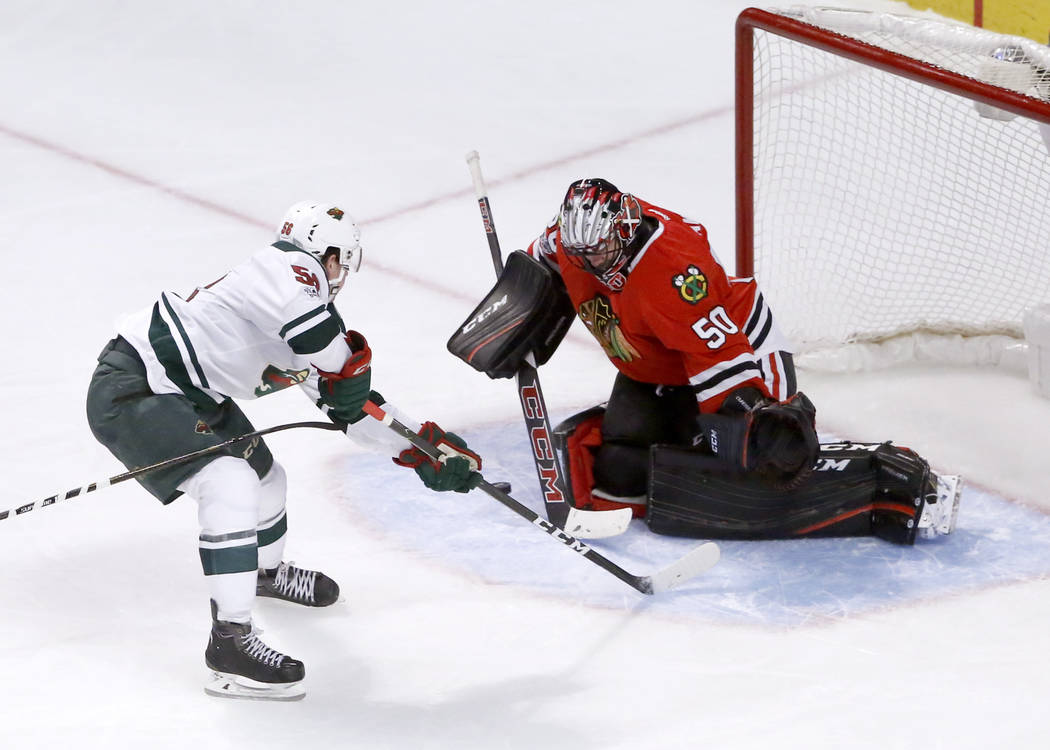 Chicago Blackhawks goalie Corey Crawford (50) makes a save on a point-blank shot by Minnesota Wild's Erik Haula during the third period of an NHL hockey game Sunday, March 12, 2017, in Chicago. (A ...