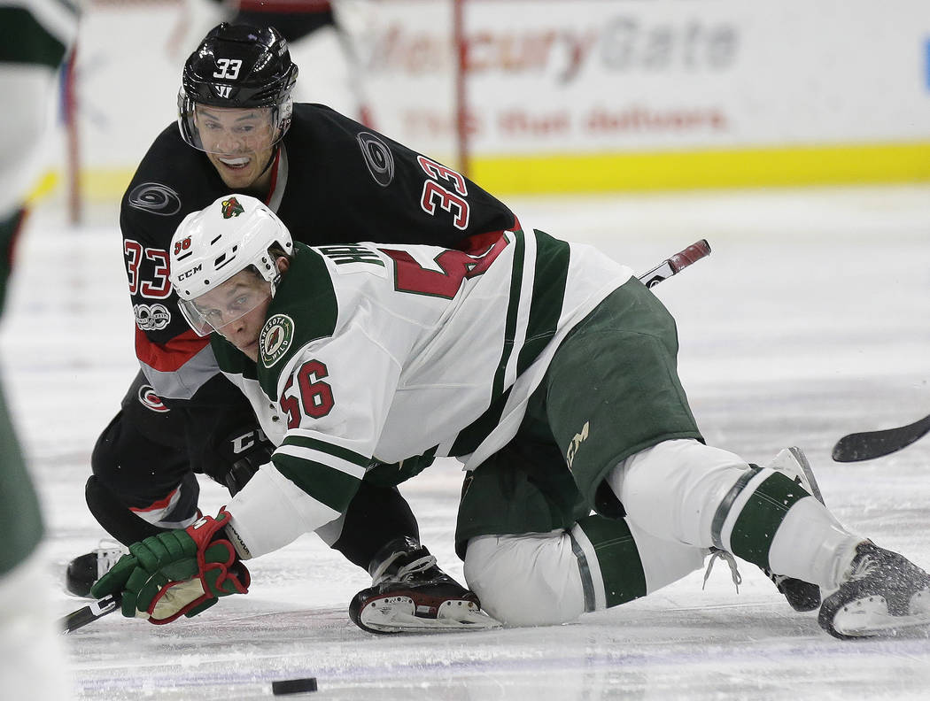 Carolina Hurricanes' Derek Ryan (33) and Minnesota Wild's Erik Haula (56), of Finland, struggle for possession of the puck during the second period of an NHL hockey game in Raleigh, N.C., Thursday ...