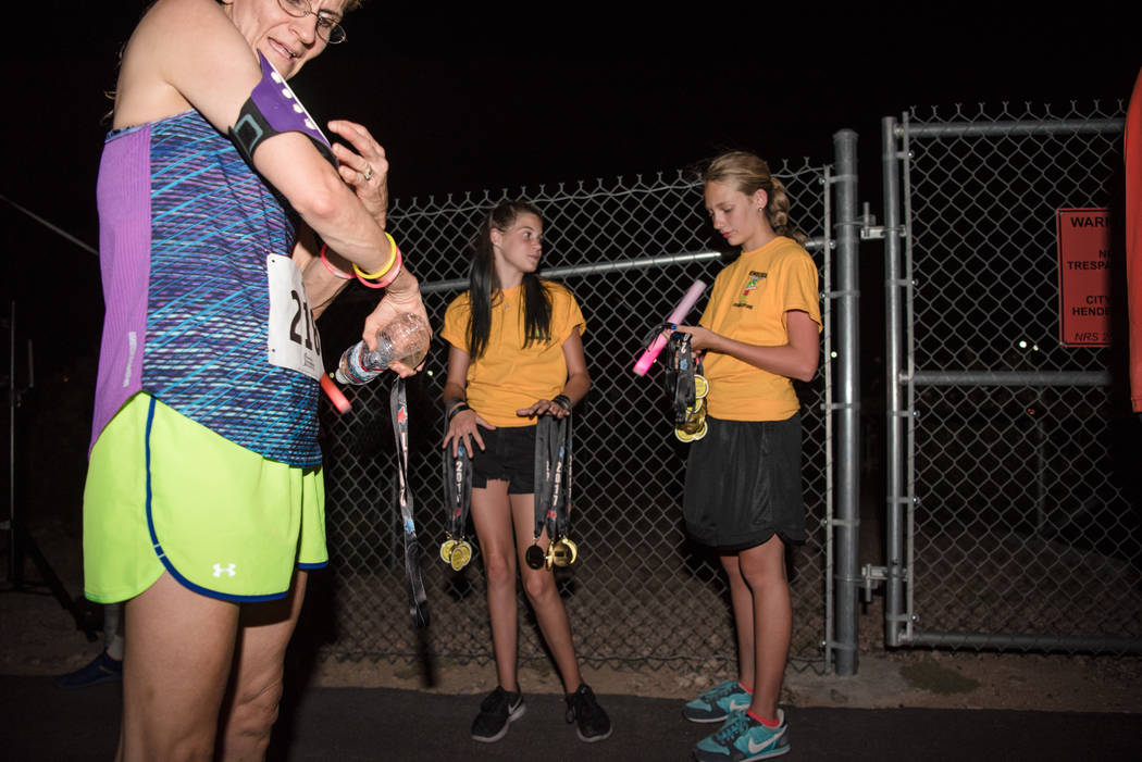 Emily Seaman, left, and Anika Hermes, right, prepare to hand out finisher medals at the Glow Worm 5K Fun Run  at Equestrian Park South and Trailhead on Saturday, June 17, 2017, in Las Vegas. (Morg ...