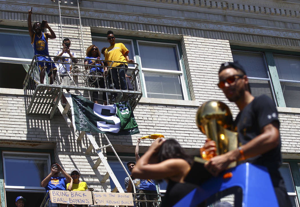 Fans watch Golden State Warriors' Stephen Curry pass by during the Golden State Warrior's victory parade and rally in downtown Oakland, Calif. on Thursday, June 15, 2017. Chase Stevens Las Vegas R ...