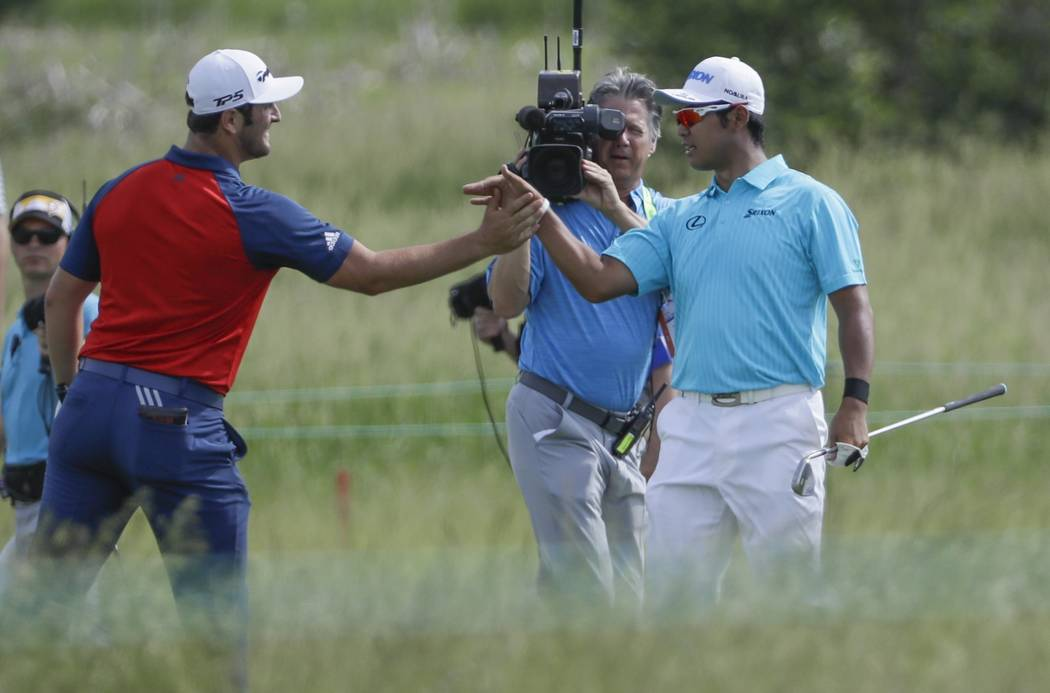 Jon Rahm, of Spain, congratulates Hideki Matsuyama, of Japan, after making a shot on the 15th hole during the first round of the U.S. Open golf tournament Thursday, June 15, 2017, at Erin Hills in ...