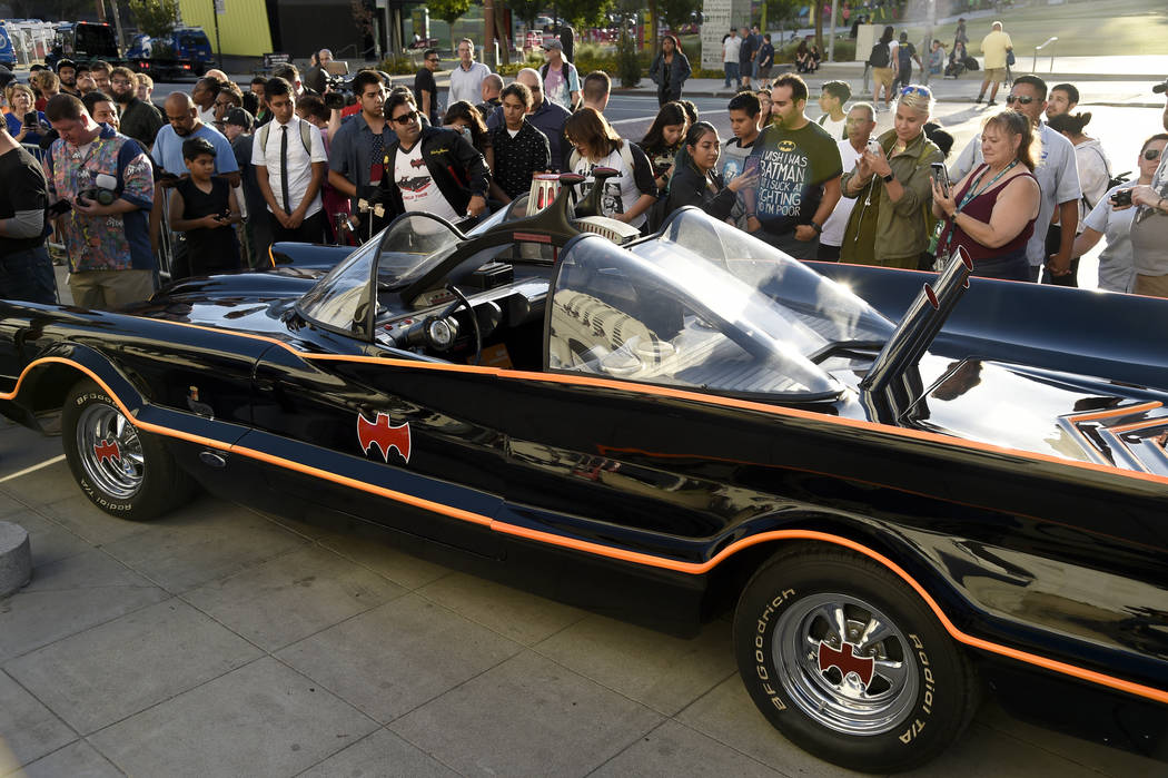 "Fans gather around a Batmobile before a tribute to ""Batman"" star Adam West that includes lighting a Bat-signal at City Hall on Thursday, June 15, 2017, in Los Angeles.  (Photo by ..."