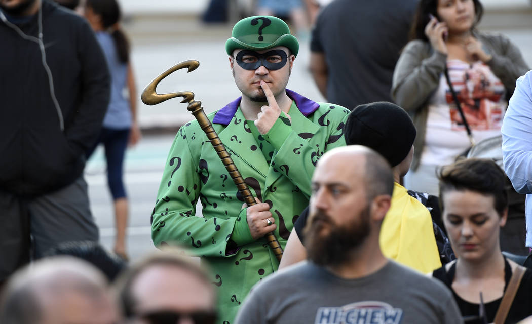 "Chat Evett, of La Junta, Colo., dressed as the Riddler, attends a tribute to ""Batman"" star Adam West that includes lighting a Bat-signal at City Hall on Thursday, June 15, 2017,  ..."
