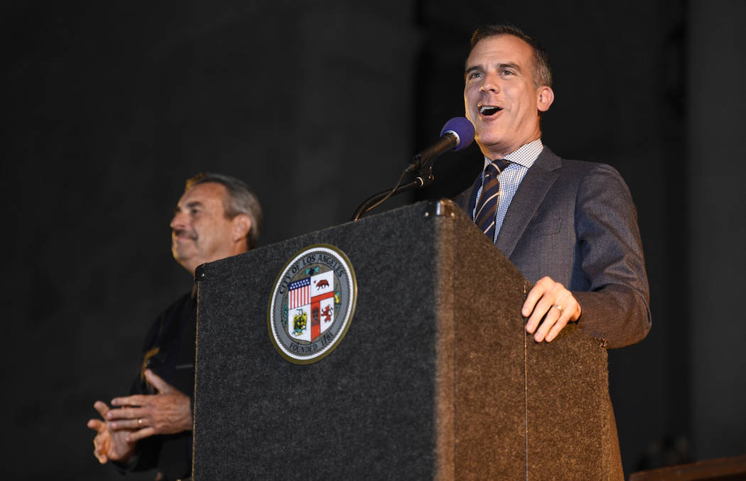"Los Angeles Mayor Eric Garcetti speaks as Los Angeles Police Chief Charlie Beck looks on at a tribute to ""Batman"" star Adam West that includes lighting a Bat-Signal at City Hall  ..."