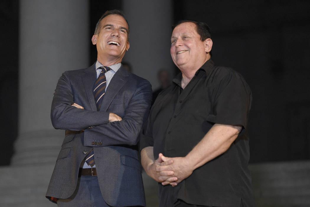 "Los Angeles Mayor Eric Garcetti, left, and ""Batman"" co-star Burt Ward appear at a tribute to ""Batman"" star Adam West that included lighting a Bat-Signal at City ..."