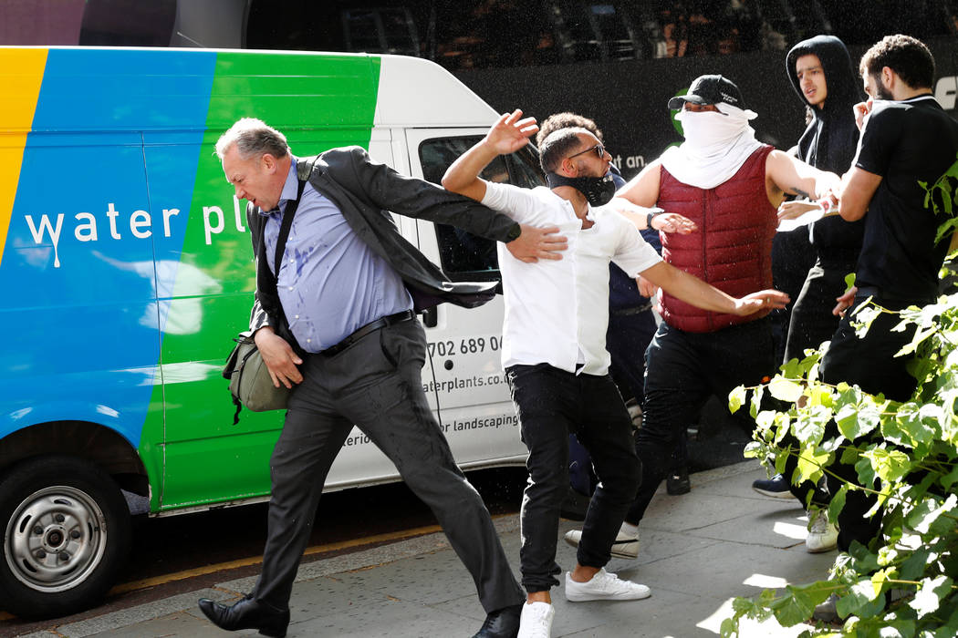 Demonstrators confront a man they believe to be Robert Black, the Chief Executive of KCTMO, outside Kensington Town Hall, during a protest following the fire that destroyed The Grenfell Tower bloc ...