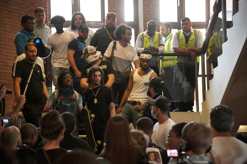 Demonstrators are watched by security personnel on a staircase after they entered Kensington Town Hall, during a protest following the fire that destroyed The Grenfell Tower block, in north Kensin ...