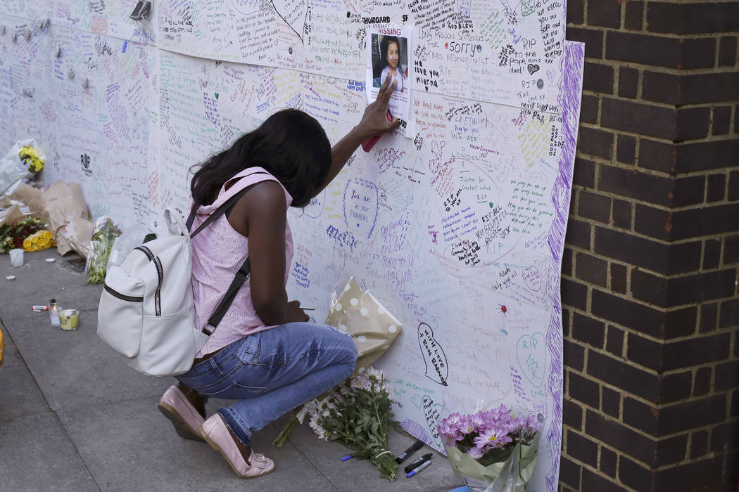 A woman touches a missing poster for 12-year-old Jessica Urbano on a tribute wall after laying flowers on the side of Latymer Community Church next to the fire-gutted Grenfell Tower in London, Fri ...